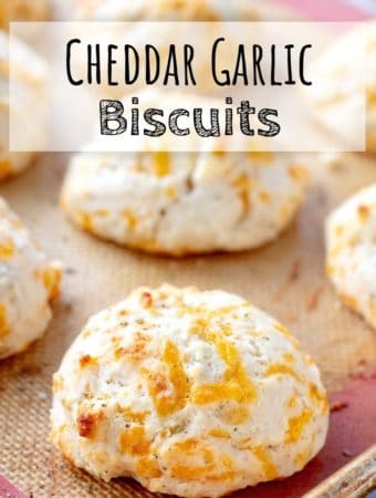 Baked Cheddar Garlic Biscuits on a baking mat with text overlay.