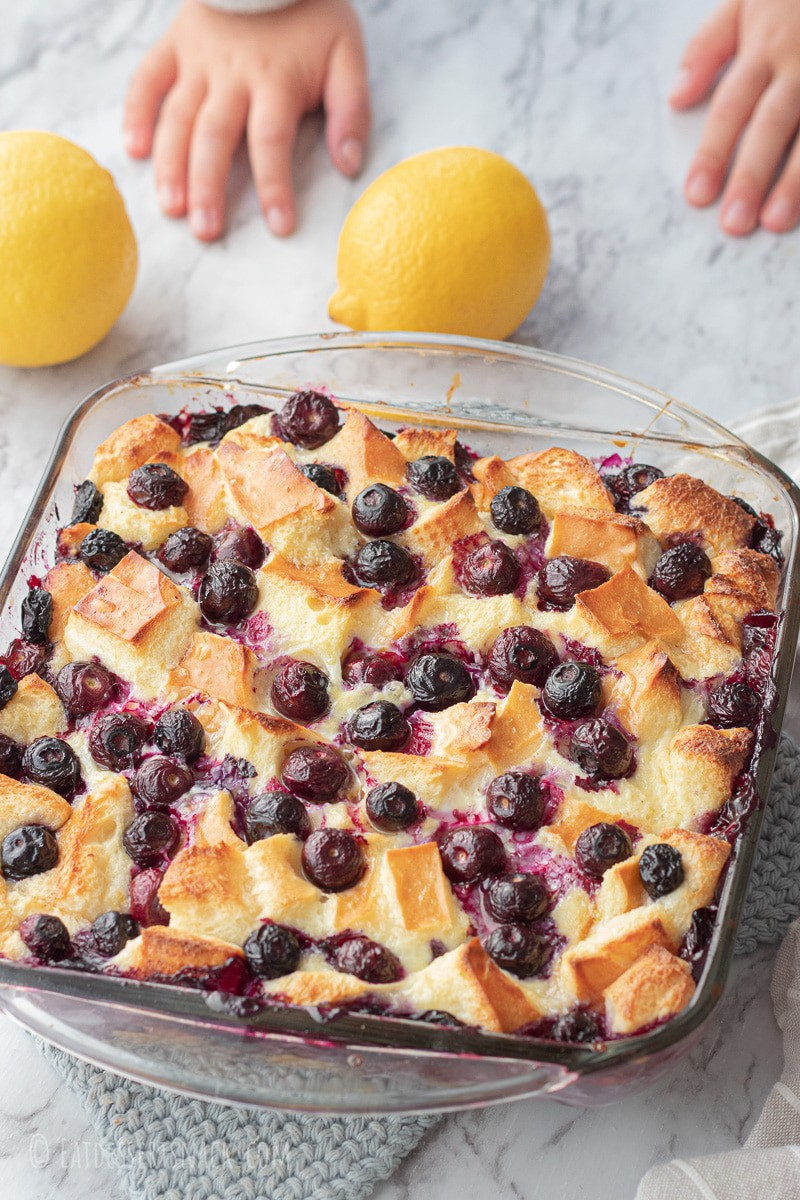 baked bread pudding with blueberries in glass pan with lemons.