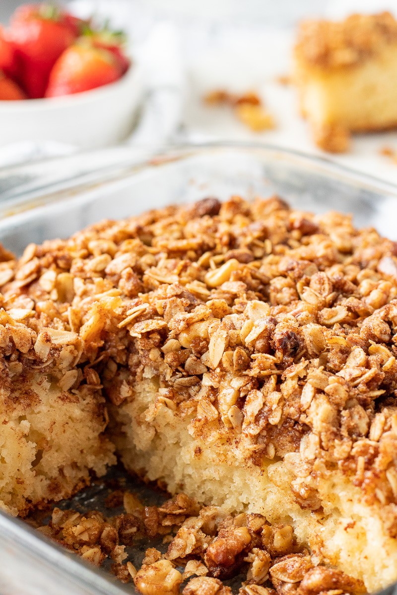 Baked classic coffee cake in a glass pan with strawberries.