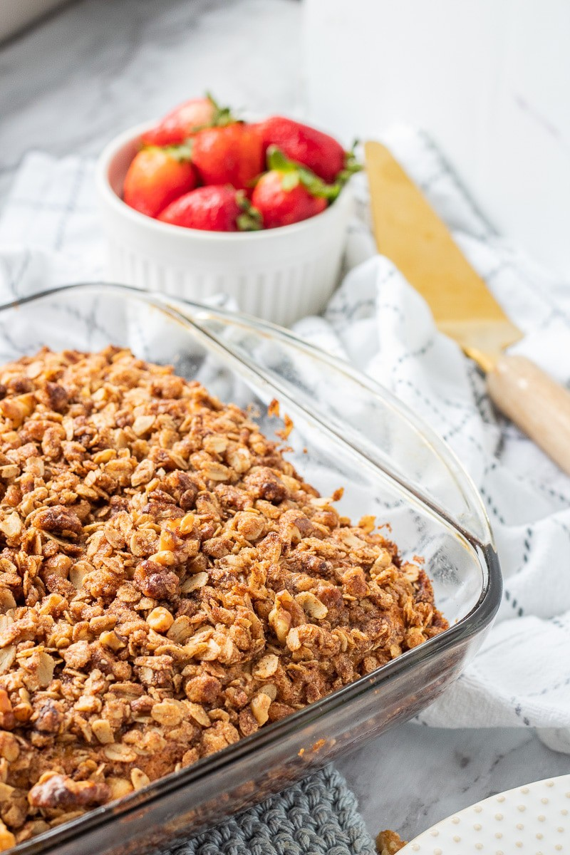 Baked Coffee cake unsliced with strawberries, spatula, and white dishtowel..