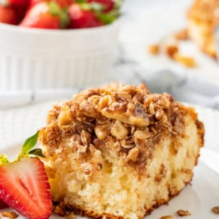 Slice of classic coffee cake on a white plate with strawberry.