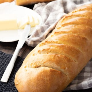 Baked loaf of fluffy french bread with butter.