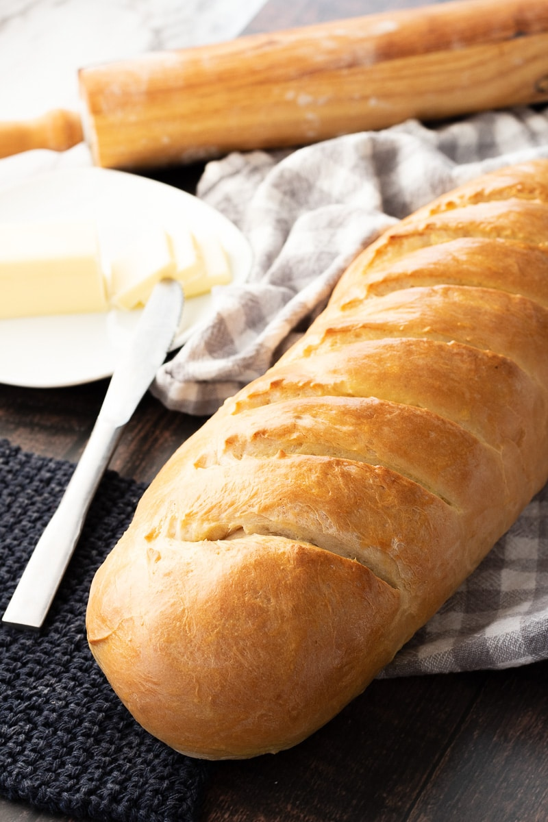 Baked crusty French bread on a dish towel with butter and rolling pin.