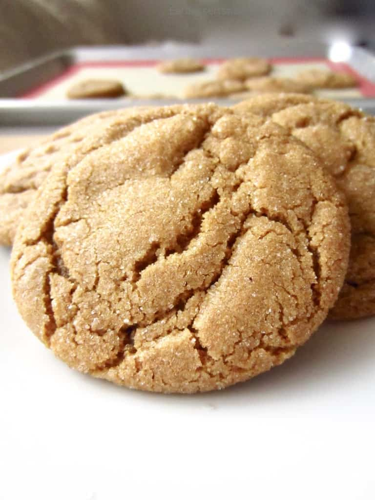 Baked ginger snap cookies in front of a pan of baked cookies.