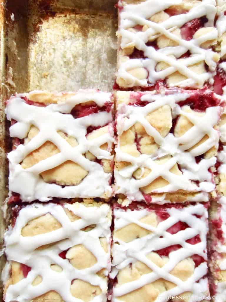 Slices of raspberry dessert bars on a metal pan.
