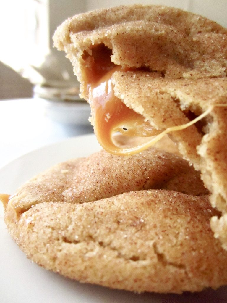 Half of a baked caramel snickerdoodle cookie with caramel dripping out.