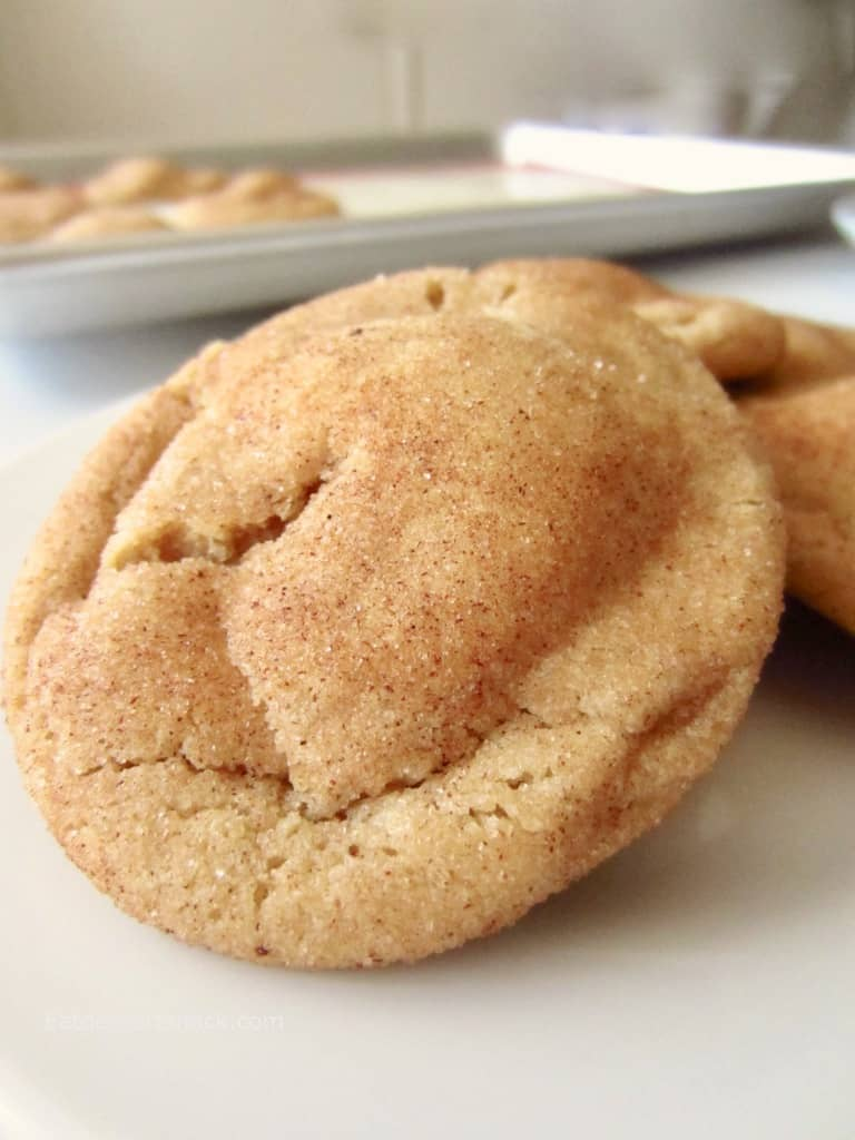 Baked caramel sugardoodle cookie in front of a pan of baked cookies.