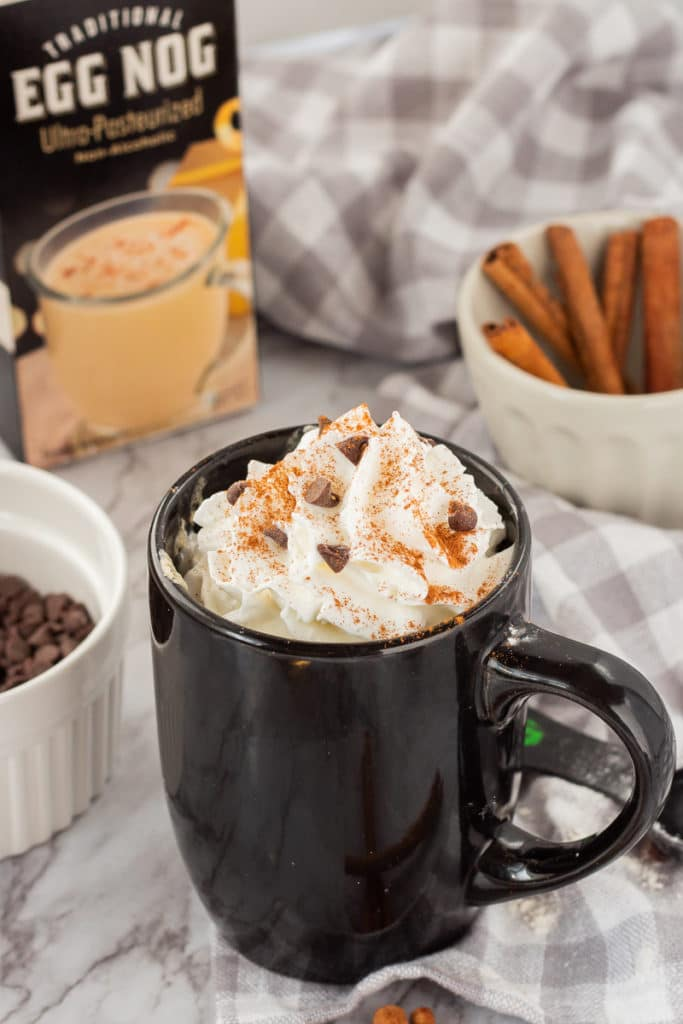 Cooked Eggnog mug cake topped with whipped cream, cinnamon, and chocolate chips.
