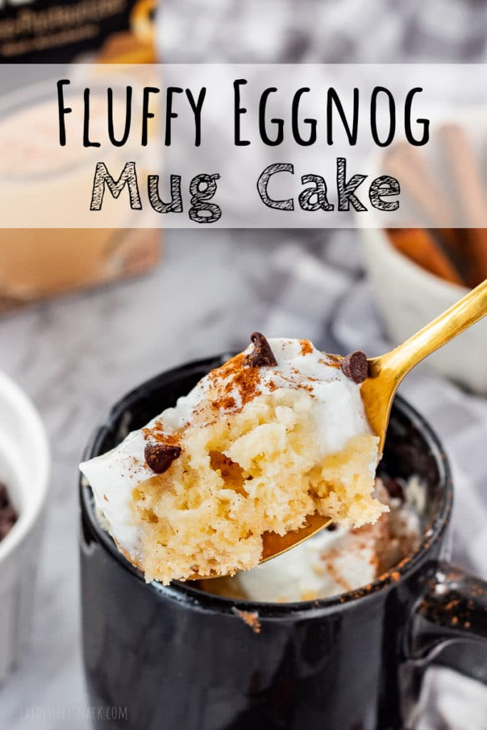 Spoon full of mug cake with whipped cream on top and mug in the back.