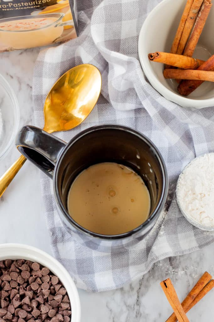 Raw ingredients around a black mug. Liquid ingredients inside mug.