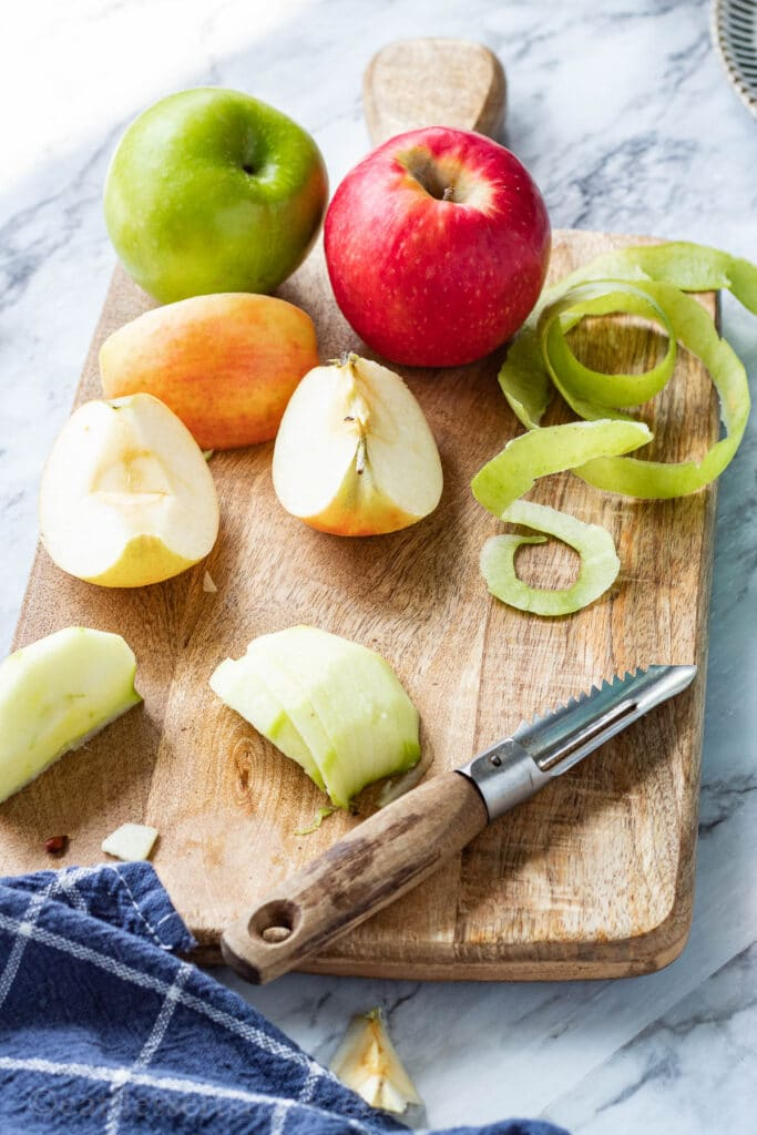 Sliced apples with peels on wood cutting board with blue towel.