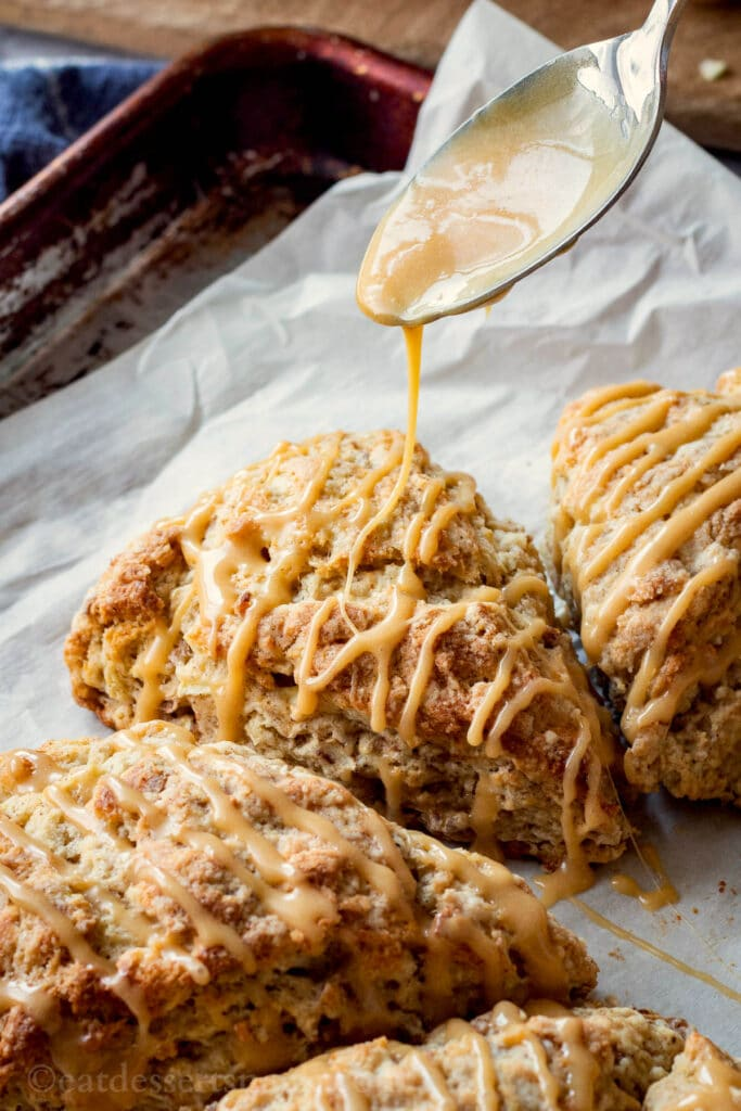 Drizzling maple caramel glaze on apple cinnamon scones.