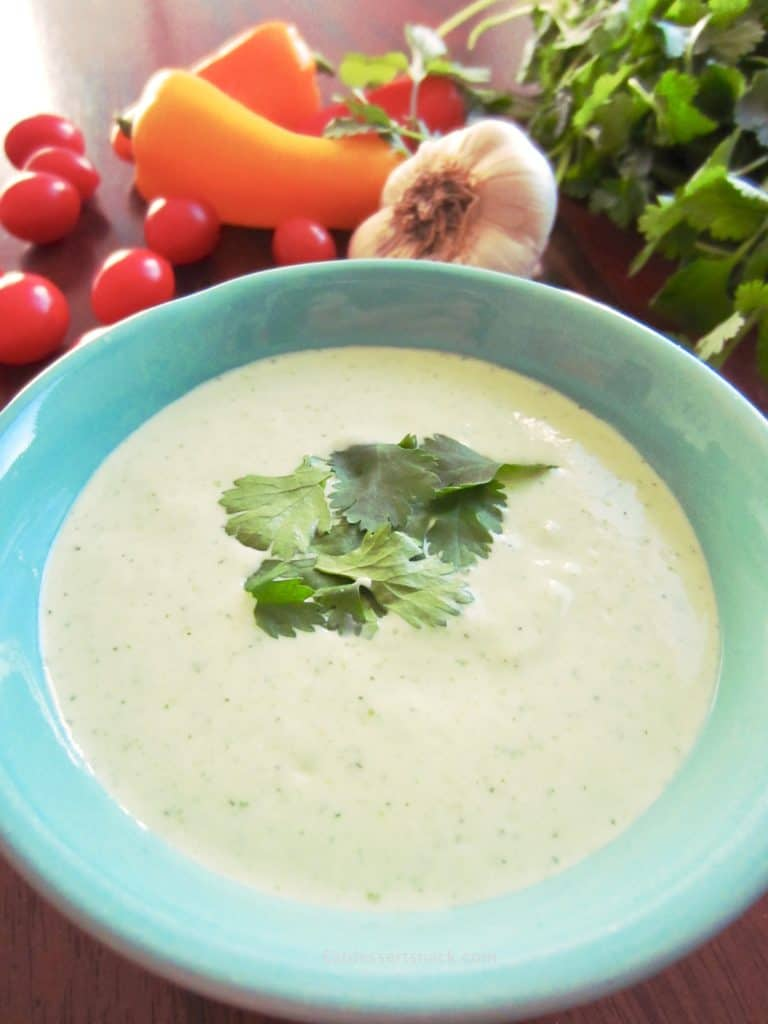 Creamy Cilantro Lime Tomatillo Ranch with Yogurt in a bowl and ingredients in the background.