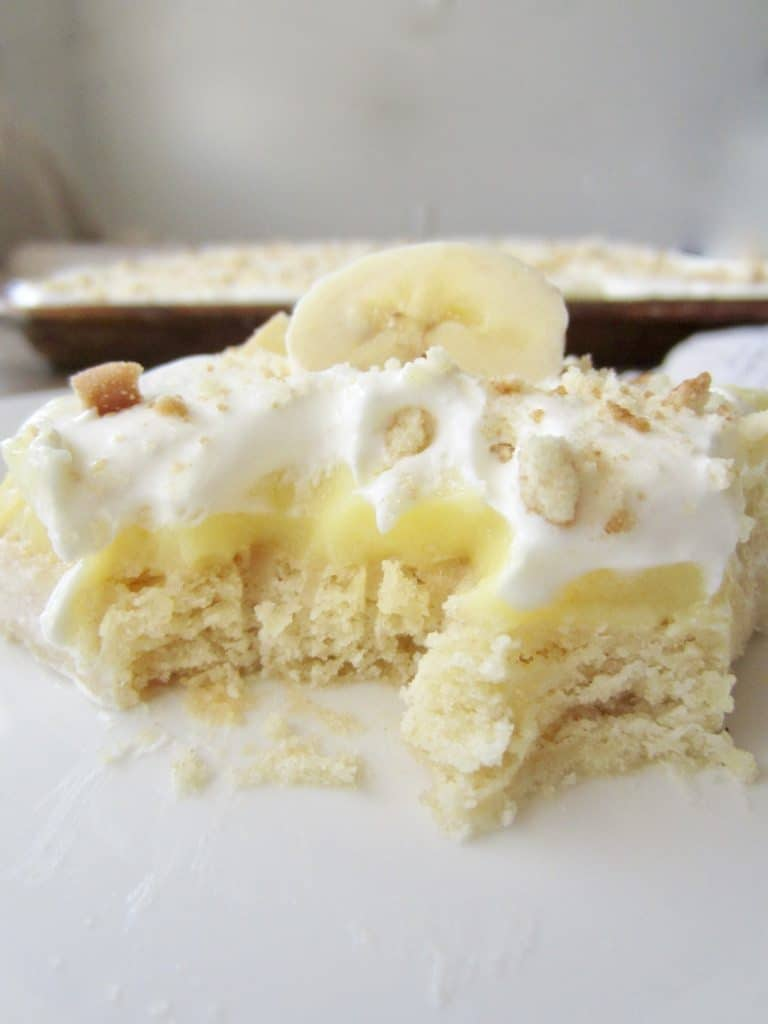 Slice of banana cream pie bar on a plate with a bite out of it.