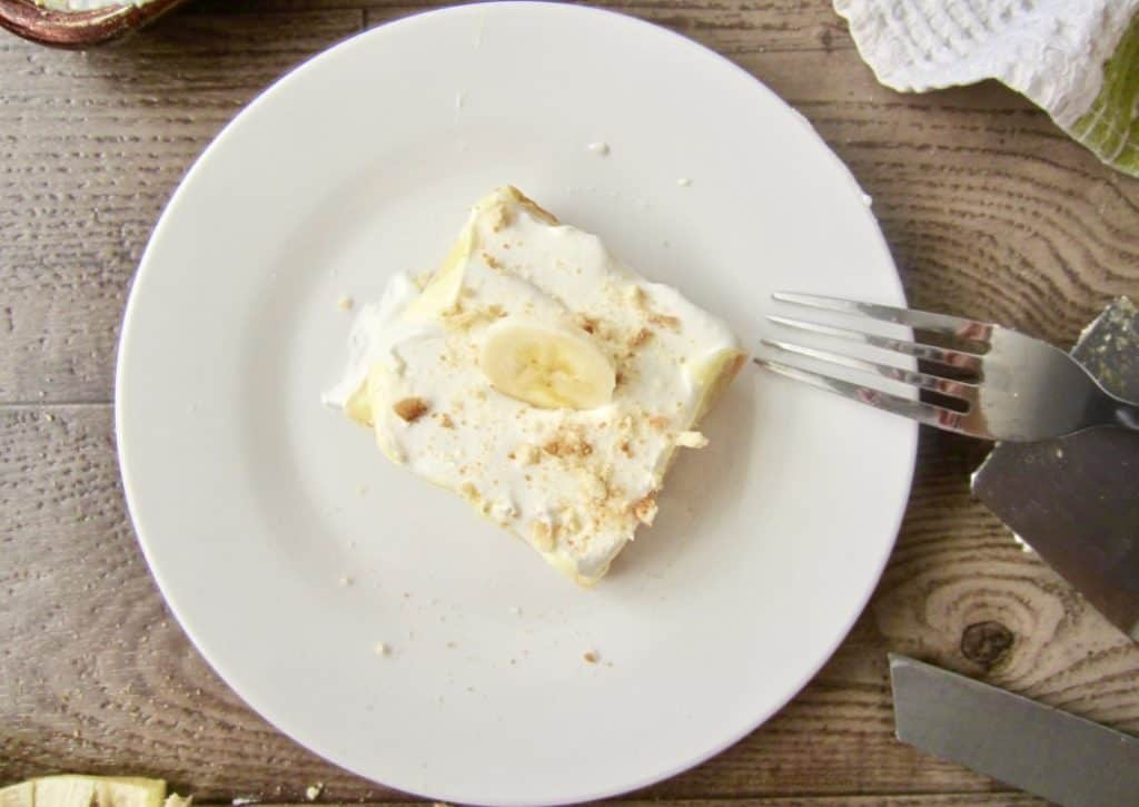 Slice of banana cream pie bar on a plate with a fork.