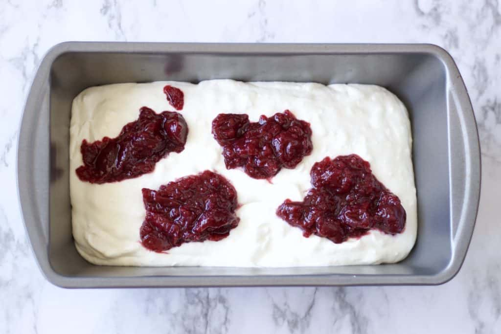 whipped cream in a pan with cherry pie filling spooned on top.