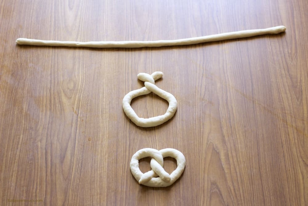 Stages of raw pretzel dough being twisted into shape on a brown table.