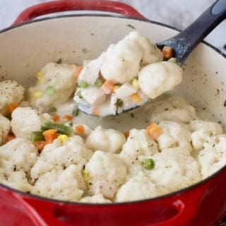 Creamy Chicken and Dumplings being spooned out of a red pot.