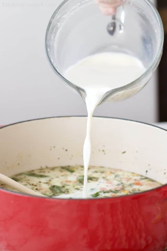 Milk mixed with flour being poured into a red pot of Creamy Chicken and Dumplings. #crockpotrecipes