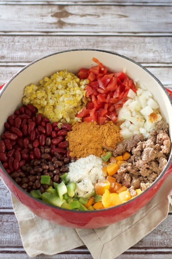 Beans, Corn, Bell Peppers, Onion, cooked ground beef, and seasonings raw in a Red Cooking Pot on a wood background.