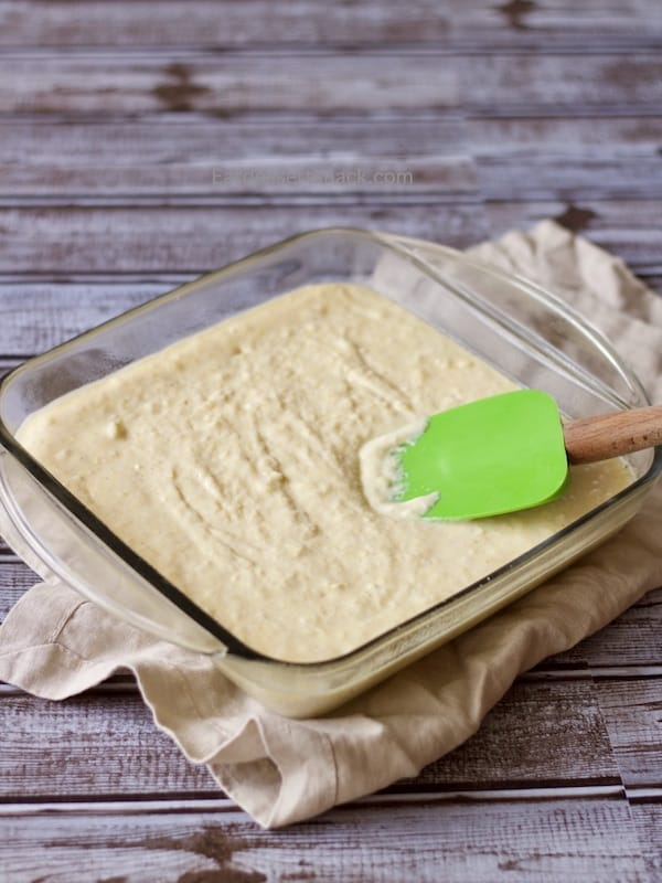 Sweet Corn Bread batter with in a glass pan with a spatula.