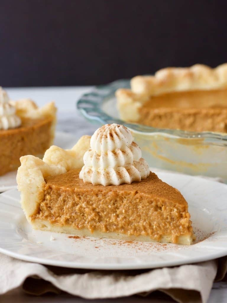 Best Pumpkin Pie slice on a plate with whipped cream and black background. Glass pie pan behind slice of pie.