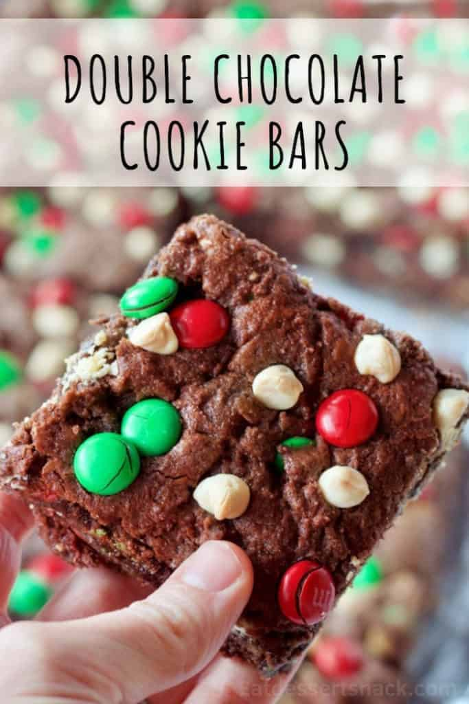 baked Double Chocolate Cookie Bars slice in hand with red and green m&m's on top.