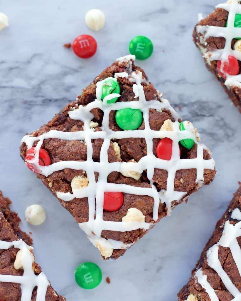 Iced and sliced square of double chocolate cookie bar square with red and green m&m's around it on a marble background.