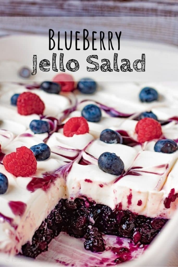 sliced blueberry jello salad with whipped cream and berries on top.