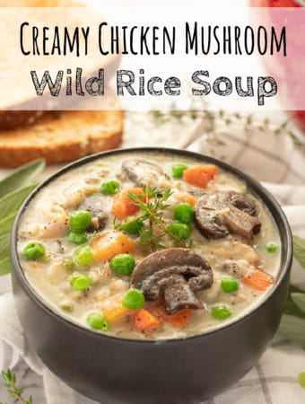 Black bowl with cooked chicken mushroom wild rice soup.
