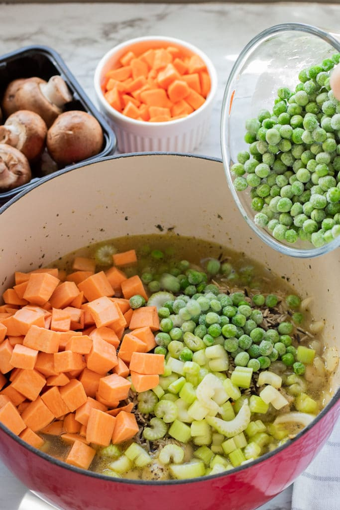 Pouring vegetables into pot of cooked chicken, wild rice, and chicken broth.