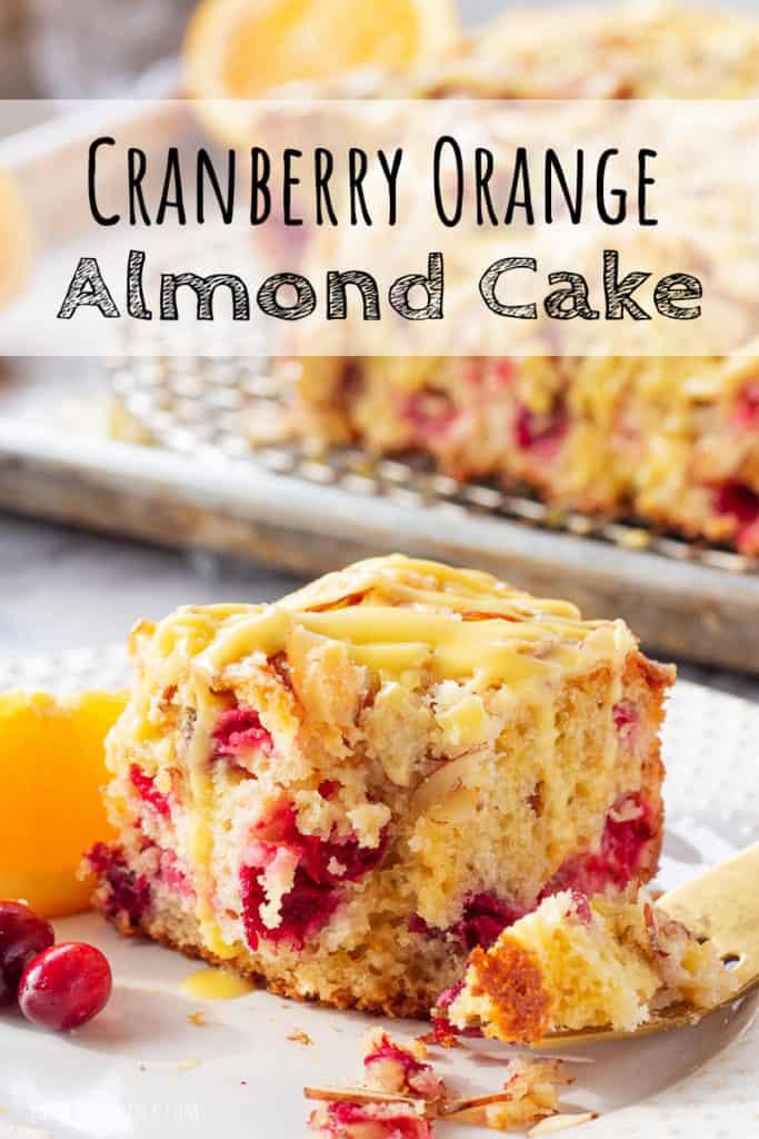 Slice of baked Cranberry Orange Almond Cake on white place with slice of orange.