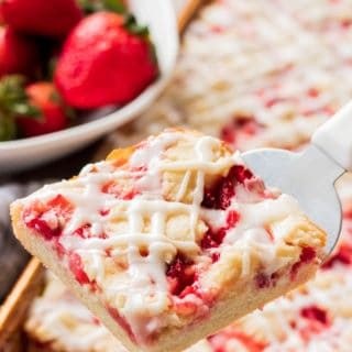 Slice of Strawberries and Cream Bar above a pan and strawberries.