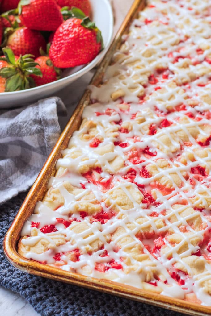 baked strawberries and cream bars by bowl of strawberries.