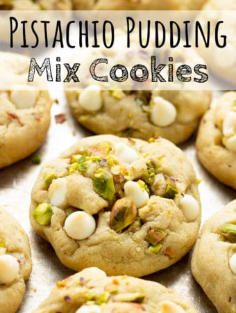 Baked pistachio pudding mix cookies with white chocolate on a baking sheet.
