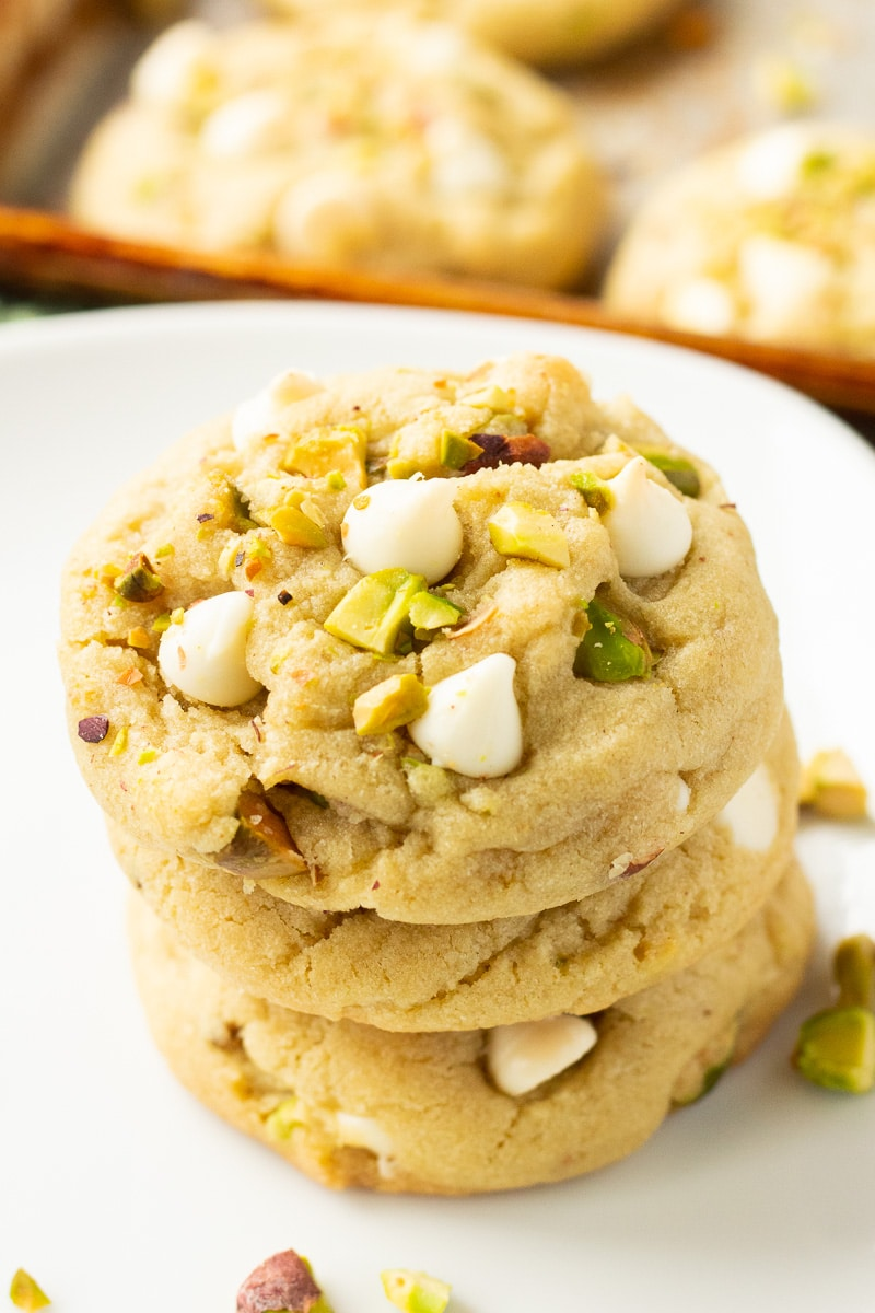 3 stacked pistachio pudding mix cookies on a white plate with pistachio crumbles and white chocolate ships.