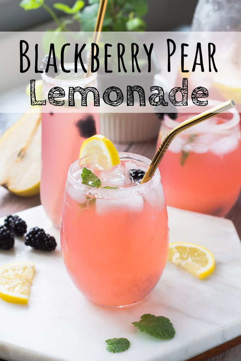 Glass cup of blackberry pear lemonade with lemon slice and gold straw.