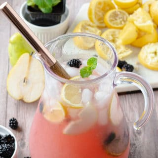 Glass pitcher of pink blackberry pear lemonade with spoon