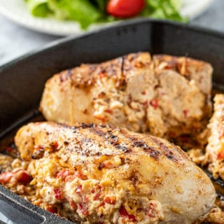 Cooked Pepperjack stuffed chicken breast in cast iron pan.