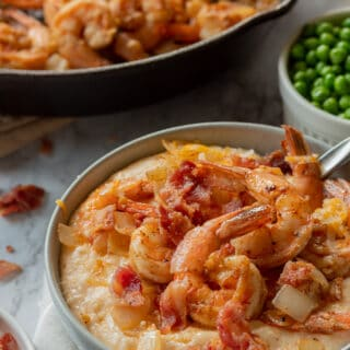 Cooked cheesy grits with shrimp, bacon and cheese on top in a gray bowl.