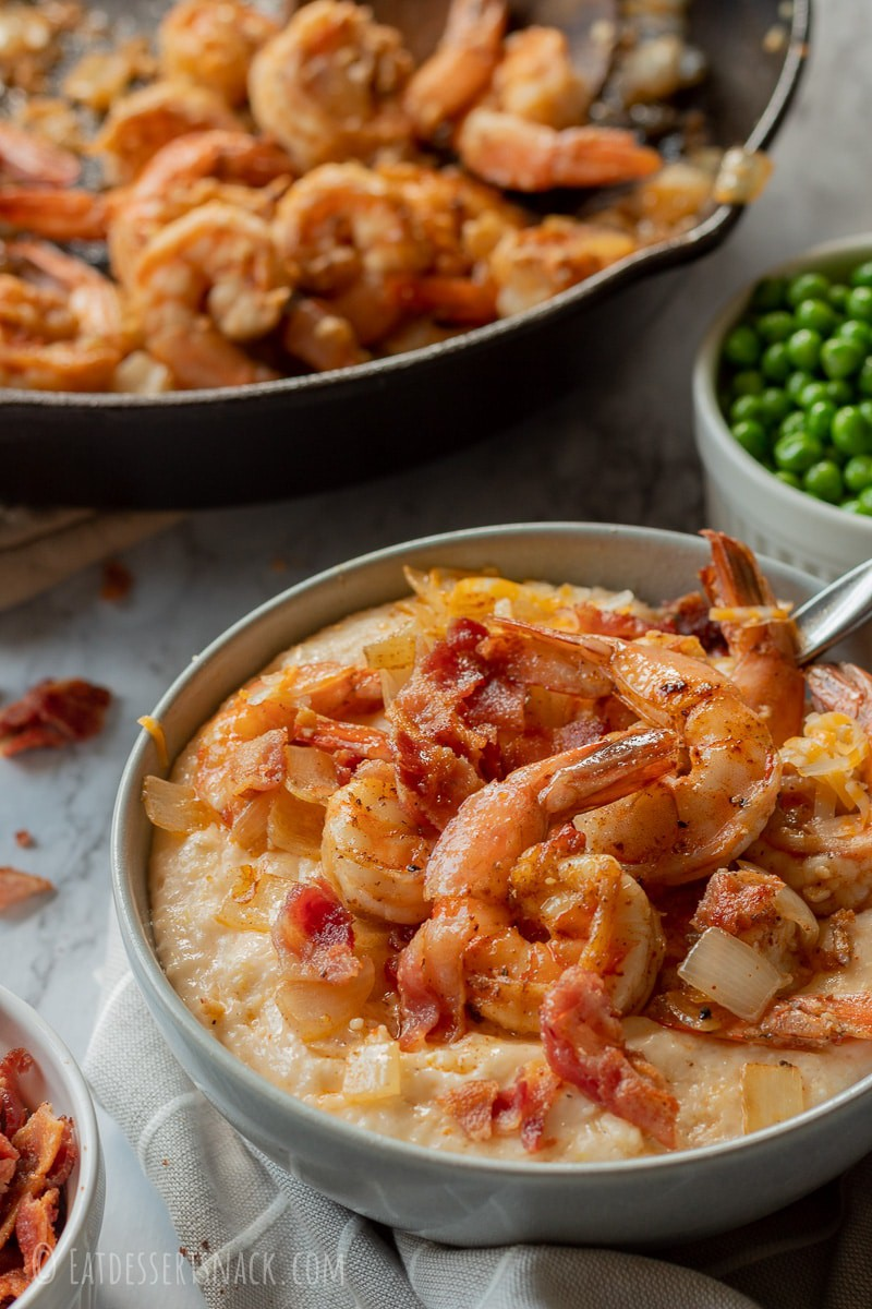 Gray bowl with cheesy grits, shrimp, and bacon with a cast iron pan filled with shrimp.