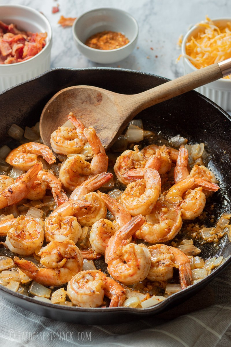 Cooked shrimp and onions in a cast iron pan with wooden spoon.