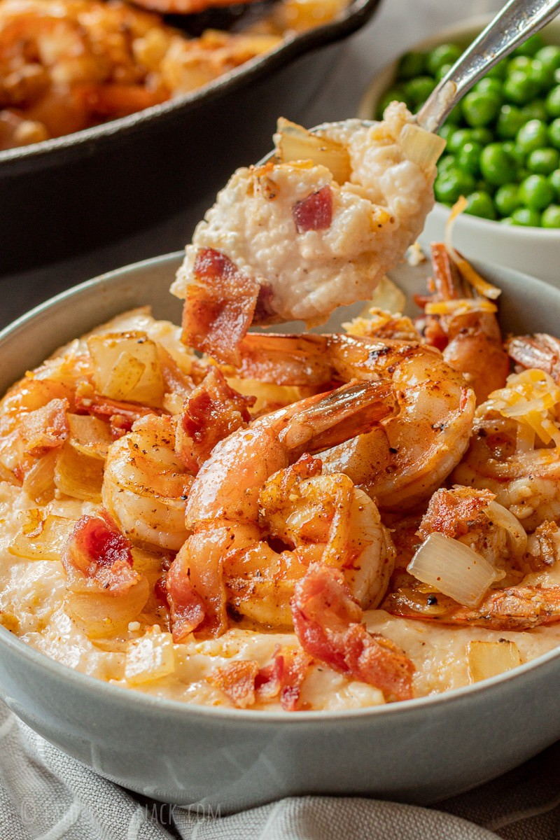 Spoonful of cheesy grits above cooked grits and shrimp in gray bowl.