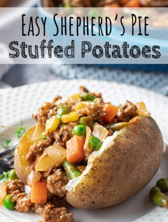 Cooked beef and vegetables in a baked potato on a white plate.