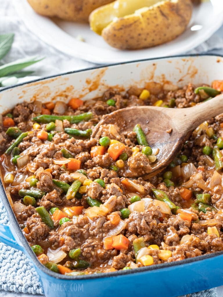 Cooked shepherd's pie filling: ground beef, mixed vegetables, in sauce with a wooden spoon.