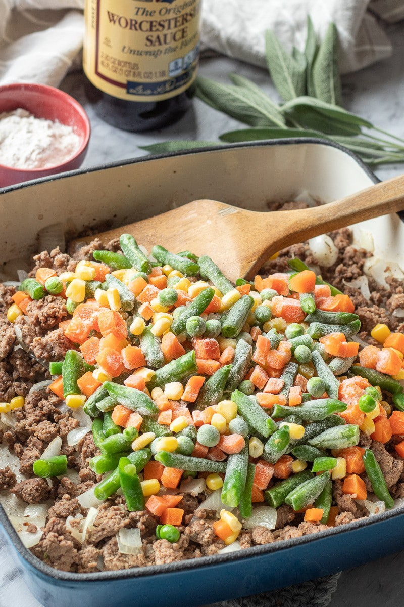 Cooked ground beef with onions, frozen peas, carrots, green beans, and corn.