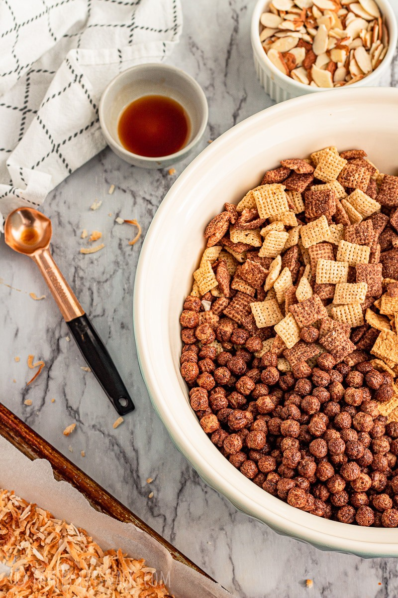 toasted coconut in a pan, vanilla in gray bowl, copper measuring teaspoon, cocoa puffs and chocolate chex in a large bowl, almonds in a white bowl.