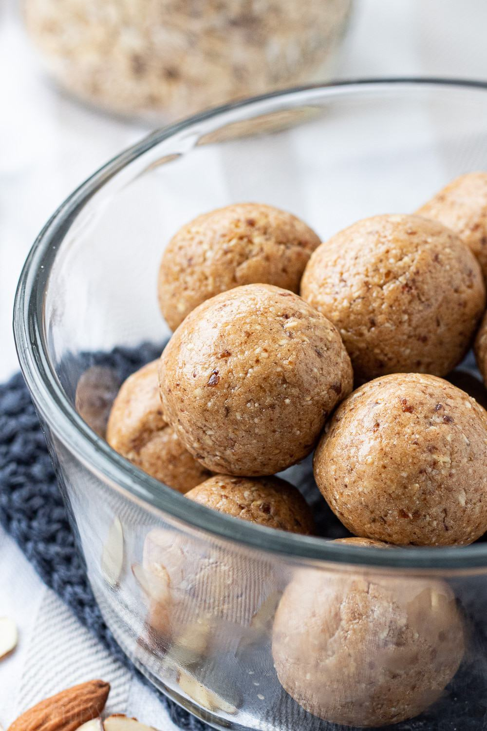 Clear bowl full of almond butter protein balls.