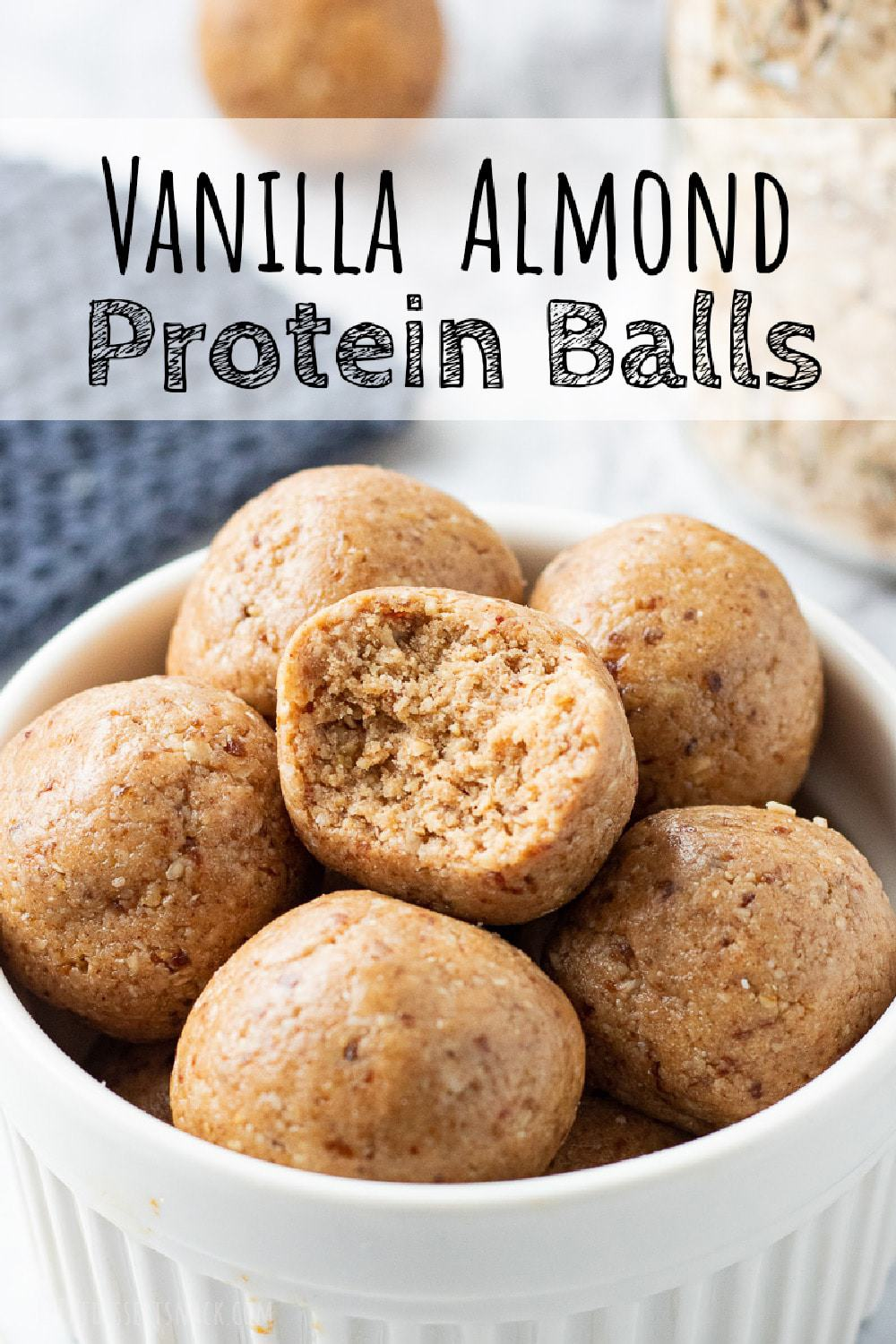 Almond Butter Protein Ball with bite mark in white bowl.