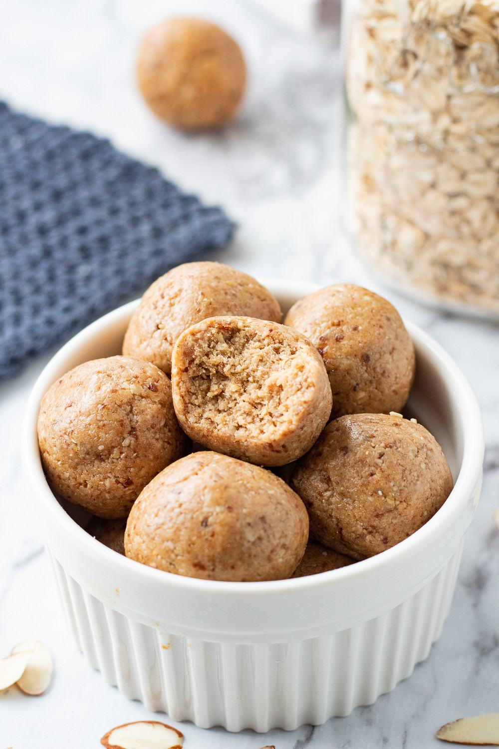 7 almond butter protein balls in a white bowl with slivered almonds.